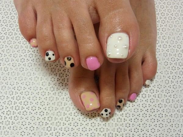 unas pies decoradas con puntos piedras